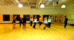 Image displays one of UMBC's physical Education Classes, with the teacher leading the class in jumping jacks.