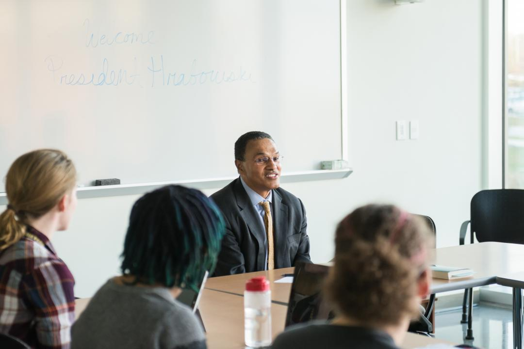 UMBC President Dr. Freeman Hrabowski sits at a table with three students